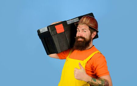 Repairman in overall hold toolbox giving thumbs up. Man with tool box. Builder in protective helmet with toolbox. Tools for repair. Repair. Handyman concept. Repair kit. Builder man carrying tool box