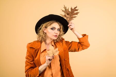 Autumn girl in black hat. Beautiful model girl with autumnal leaves. Sensual woman with autumn leaf in orange jacket. Woman autumn fashion. Fashionable woman with autumn leaves in hand. Fall. October Stockfoto