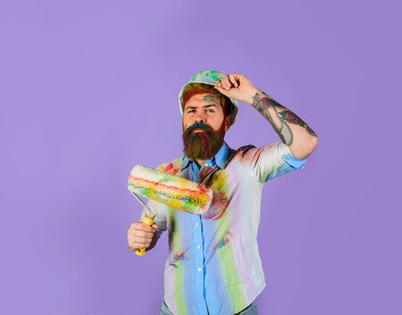 Painter. Repairman, tradesman, handyman with paint roller and helmet. Professional painter, decorator, builder worker. Repair, building concept. Handsome bearded worker with paint roller and hard hat