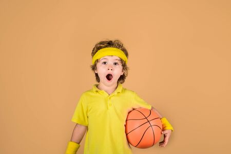 Sport active. Kid holds basketball. Sporty boy with ball. Boy in sportswear. Sport, fitness, healthy lifestyle. Sport for children. Basketball player. Kid playing with basketball. Hobby sport concept