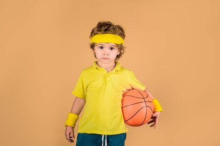 Sport active. Hobby sport concept. Kid holds basketball. Sporty boy with ball. Boy in sportswear. Sport, fitness, healthy lifestyle. Sport for children. Basketball player. Kid playing with basketball