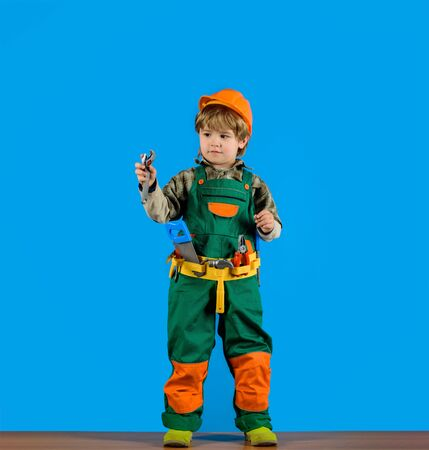 Repair concepr. Little boy with toy helmet and tools. Construction worker. Builder. Little repairman. Child game. Tools for building. Kid playing with repair tools Stockfoto