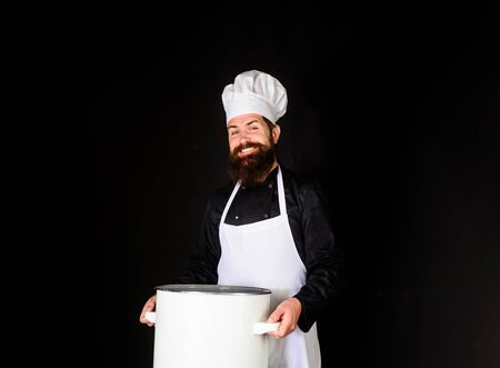 Chef in uniform cooking with casserole. Cooking pot. Chef, cook or baker with saucepan in hand. Professional chef in uniform and hat holds pan. Male chef holds pot. Cooking, food, profession concept