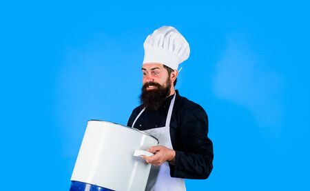 Male chef cooking with cooking pot. Casserole. Chef, cook or baker with saucepan in hand. Professional chef in uniform and hat holds pan. Chef in uniform holds pot. Cooking, food, profession concept
