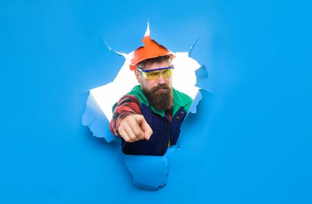 Bearded man in construction helmet through hole in paper pointing at you. Construction worker in hardhat&protective glasses. Builder in hard hat shows finger on you. Mechanical worker points forward