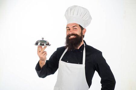 Chef cook holds metallic dish. Cook holds cloche in restaurant. Cooking. Restaurant serving. Presentation. Male chef presenting silver tray. Serving and presentation. Bearded chef holds food tray