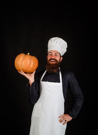 Autumn vegetables. Healthy vegetarian eating. Chef preparing meal in kitchen. Big pumpkin for Halloween. Fresh Pumpkin. Harvest pumpkin. Bearded cook in chef hat with pumpkin. Diet food. Farm market Stockfoto