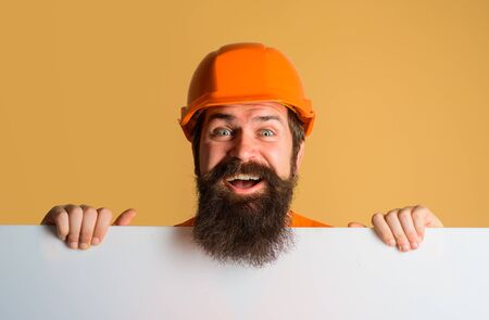 Construction worker, engineer, architect with blank board. Man builder holds advertising banner, billboard, sign board. Builder, repairman in protective helmet holds empty board with space for text