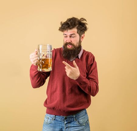 Bearded man drinking beer from glass at bar or pub. Stylish man with beard holds mug of beer. Drinks, alcohol, leisure and people concept. Bad habits. Bearded drunk hipster male holds craft beer