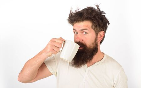 Morning refreshment and drink. Refreshment and energy. Bearded man with white coffee cup. Tired sleepy man with beverage in cup. Handsome bearded young man drinking coffee or tea. Breakfast concept