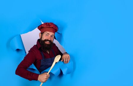 Bearded cook with wooden spoon looking through paper. Bearded man chef preparing to cook food. Handsome chef cook with kitchen utensils. Chief man in cook uniform holds wooden kitchen cooking tools Stockfoto