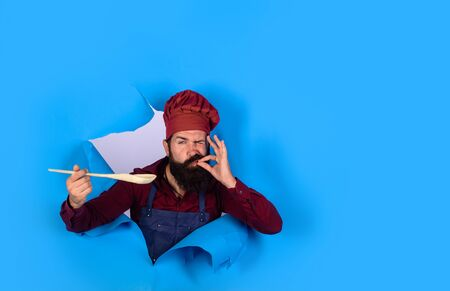 Bearded man chef preparing to cook food. Handsome chef cook with kitchen utensils. Chief man in cook uniform with wooden spoon looking through paper. Bearded cook holds wooden kitchen cooking tools