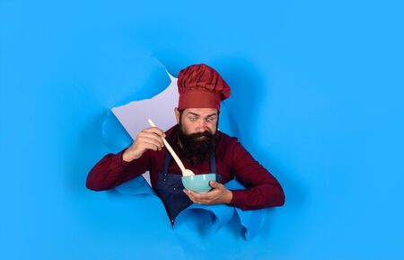 Healthy ration. Chef wear hat and apron looking through paper hole. Healthy food. Eat healthy. Man professional chef hold bowl and spoon. Dieting concept. Bearded chef in uniform. Cook preparing food