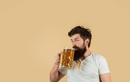 Bearded man drinking beer from glass at bar or pub. Craft beer at restaurant. Oktoberfest festival. Drink, alcohol, leisure and people concept. Bearded male tasting fresh brewed beer. Beer in Germany