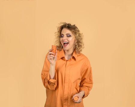 Enjoying healthy food. Beautiful girl eating carrot. Vegetable having good impact on teeth. Smiling woman bites carrot. Happy woman with organic carrot. Healthy eating, vegetarian food, diet, dieting