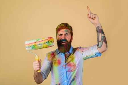 Painter man pointing finger up. Repairman, tradesman, handyman with paint roller. Repair, building concept. Handsome bearded worker with paint roller. Professional painter, decorator, builder worker