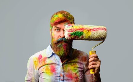 Painter man. Professional painter, decorator. Repair, building concept. Room painting job. Handsome bearded worker with paint roller. Builder worker, repairman, tradesman, handyman with paint roller