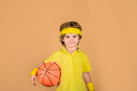 Kid holds basketball. Sporty boy with ball. Sport active. Boy in sportswear. Sport, fitness, healthy lifestyle. Sport for children. Basketball player. Kid playing with basketball. Hobby sport concept
