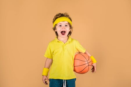 Boy in sportswear throws ball. Cute little boy holds basketball ball. Adorable child playing basketball. Basketball player with ball. Little kid with basket ball. Basketball boy. Enjoy sport game Stockfoto