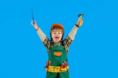 Repair concepr. Excited boy with toy helmet and tools. Construction worker. Builder. Little repairman. Child game. Tools for building. Kid playing with repair tools