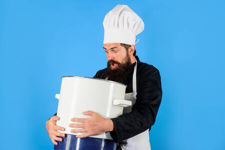 Chef, cook or baker with saucepan in hand. Cooking pot. Professional chef in uniform and hat holds pan. Male chef holds pot. Cooking, food, profession concept. Chef in uniform cooking with casserole