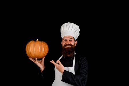 Big pumpkin for Halloween. Healthy vegetarian eating. Farm market. Autumn vegetables. Fresh Pumpkin. Harvest pumpkin. Bearded cook in chef hat with pumpkin. Diet food. Chef preparing meal in kitchen
