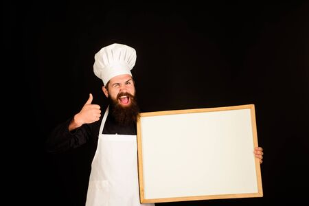 Winking chef holds blackboard shows thumb up. Man cook show empty menu chalkboard with copy space. Empty menu chalkboard with copy space for text. Chef menu. Male chef, cook or baker with blank board Stockfoto