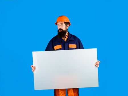 Builder, repairman in protective helmet holds empty board with space for text. Man builder holds advertising banner, billboard, sign board. Construction worker, engineer, architect with blank board