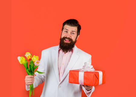 Handsome young man holding gift box and flowers. Businessman with gift and bouquet of tulips for birthday. Romantic man. Bearded man holds bouquet of flowers and gift box. Valentines Day, Womens Day