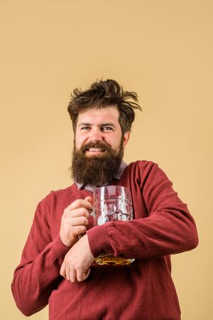 Bad habits. Drinks, alcohol, leisure and people concept. Bearded man drinking beer from glass at bar or pub. Bearded drunk hipster male holds craft beer. Stylish man with beard holds mug of beer