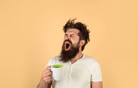 Un gars fatigué tient une tasse de café. Un homme au visage endormi essaie de se réveiller avec une tasse de café. L'homme béant tient une tasse avec une boisson chaude. Rafraîchissement du matin. L'homme endormi tient une tasse de café. Homme avec une tasse de café frais