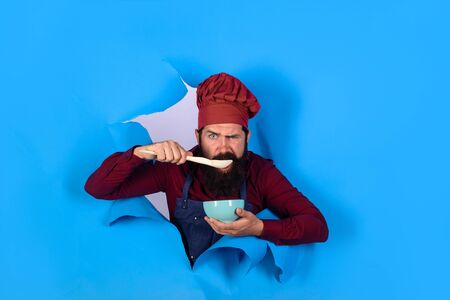 Healthy food. Eat healthy. Healthy ration. Chef wear hat and apron looking through paper hole. Man professional chef hold bowl and spoon. Dieting concept. Bearded chef in uniform. Cook preparing food