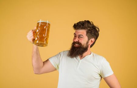 Craft beer at restaurant. Bearded man drinking beer from glass at bar or pub. Oktoberfest festival. Bearded male with craft beer. Drink, alcohol, leisure and people concept. Tasting fresh brewed beer