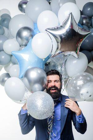 Birthday, preparing to party, celebration. Stylish birthday guy hold balloons. Happy businessman with helium balloons. Bearded man with balloons at birthday party. Handsome man with bunch of balloons Stock Photo