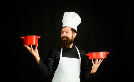 Cooking, food, profession. Bearded man cook wear chef hat and uniform. Professional chef man in cook hat. Male chef, cook, baker in uniform holds saucepan in hands. Chief man in white apron with pots