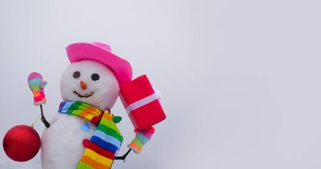 Snowman in cap, scarf in winter. Christmas and winter fashion. Winter holiday. Handmade snowman with gift. Snowman with New Year ball. Wintertime. Merry christmas and happy new year greeting card
