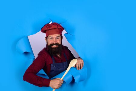 Handsome chef cook with wooden spoon looking through paper. Chief man in cook uniform holds wooden kitchen cooking tools. Bearded man chef preparing to cook food. Bearded cook with kitchen utensils