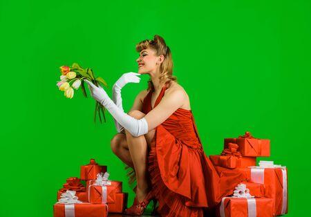 漂亮的金发女人穿着红色的裙子和复古的发型。复古女人,带着礼物盒和鲜花。微笑的复古女人捧着春天的鲜花