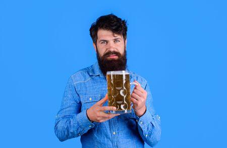 Celebration oktoberfest festival. Beer time. Bearded man holds beer glass. Handsome man drinks ale at bar or pub. Beard man drinking beer from mug.