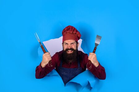 Grill cook. Chef man with BBQ cooking tools. Barbecue chef looking through paper hole.