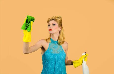 Reinigungsservice. Reinigungswerkzeuge. Glückliche Retro-Hausfrau. Hausfrau bereit für die Hausarbeit. Reinigung Pin-up-Frau. Schöne Frau hält Staubtuch und Spray. Mädchenreinigung mit Lappen- und Flaschenspray Aufräumen Standard-Bild