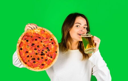 Woman eating pizza. Smiling woman holds glass with beer. Food. Lunch. Happy girl holding pizza and beer. Fastfood. Snack. Food delivery. Pizza time