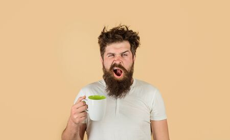 Yawning man with sleepy face try to awake with cup of coffee. Man hold mug with hot drink. Man with cup of coffee. Sleepy man holds cup of coffee. Tired guy hold coffee mug. Morning refreshment Standard-Bild