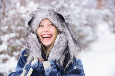 Wintertime. Close up portrait of smiling girl in snow park. Beautiful young woman in winter. Winter holidays. Beautiful girl in warm coat and fur hat. Snowy park