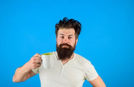 Happy man having cup of coffee in kitchen. Morning coffee concept. Bearded man holds mug with hot drink. Inspired with cup of fresh coffee. Refreshment and energy. Confident man holds tea mug Archivio Fotografico - 131437970