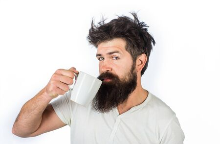 Man with cup of coffee in kitchen. Refreshment and energy. Man holds mug with hot drink. Cup of coffee. Bearded man holds tea cup. Morning coffee concept