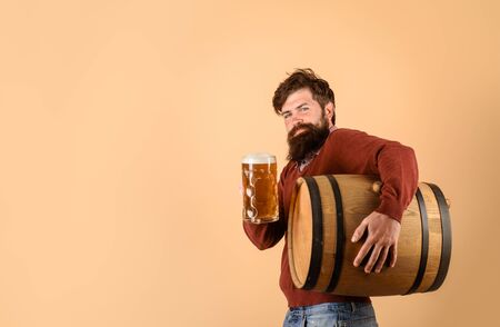 Beer time. Holliday, drinks, alcohol and leisure concept. Bearded man hold glass and barrel with craft beer. Oktoberfest festival. Attractive bearded brewer with wooden barrel of beer and mug of beer