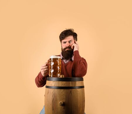 Wooden barrel of beer. Beer in Germany. Oktoberfest. Alcohol. Confused bearded man with glass with beer. Alcohol dependence
