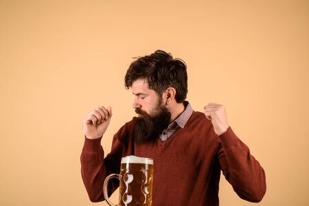 Beer pub. Beer time. Brewing. Stylish guy at cafe pub. Alcohol, harmful habits. Oktoberfest. Stylish handsome man drinking beer of glass on party. Smiling bearded hipster drinking craft beer from mug Stockfoto