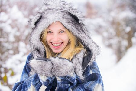 Wintertime. Close up portrait of smiling girl in snow park. Beautiful young woman in winter. Winter holidays. Beautiful woman in warm coat and fur hat. Snowy park Stock Photo